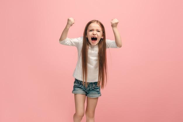 Сердитая девочка-подросток, стоящая на модном синем фоне студии. женский поясной портрет.