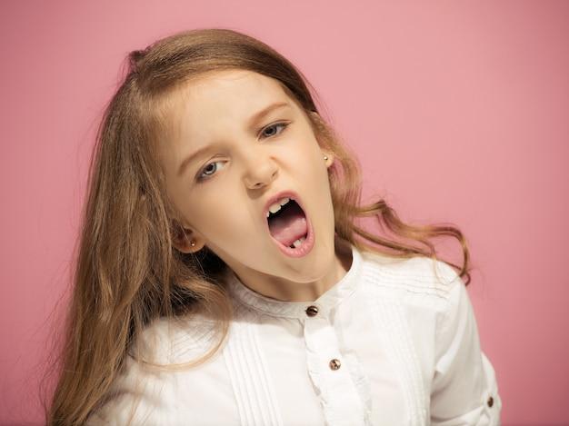 トレンディなピンクの上に立っている怒っている十代の少女。女性の半身像。人間の感情、表情の概念