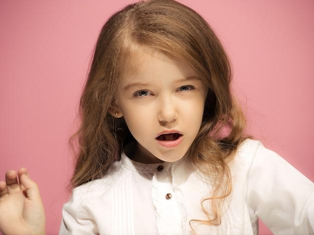 Сердитая девочка-подросток, стоящая на модном розовом фоне студии. женский поясной портрет