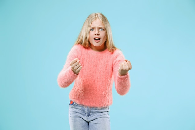 Angry teen girl standing on trendy blue studio background. female half-length portrait. human emotions, facial expression concept.