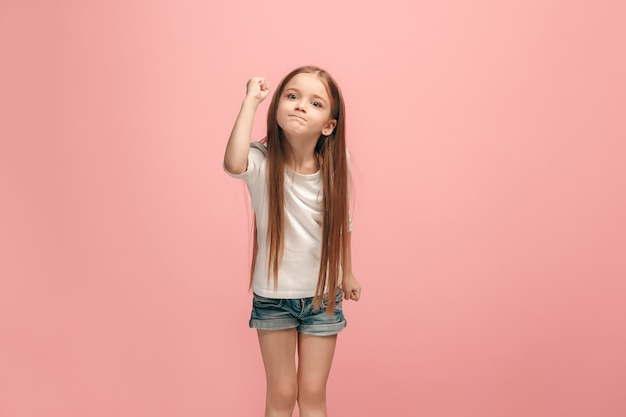 Angry teen girl standing on trendy blue studio