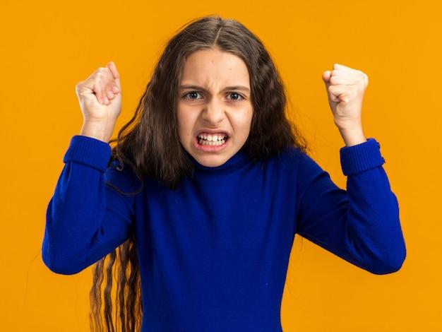 オレンジ色の壁に分離された拳を食いしばって怒っている10代の少女