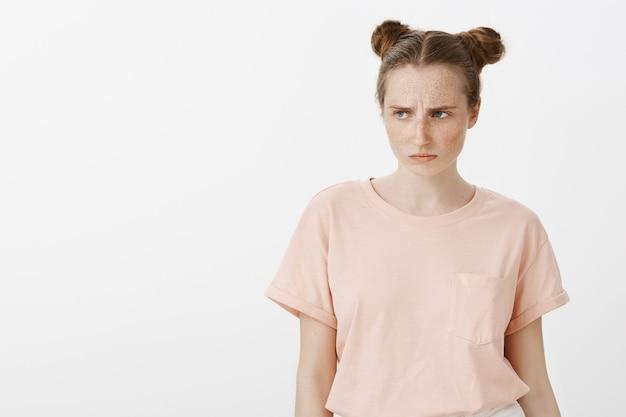 白い壁に向かってポーズをとって怒っている10代の少女