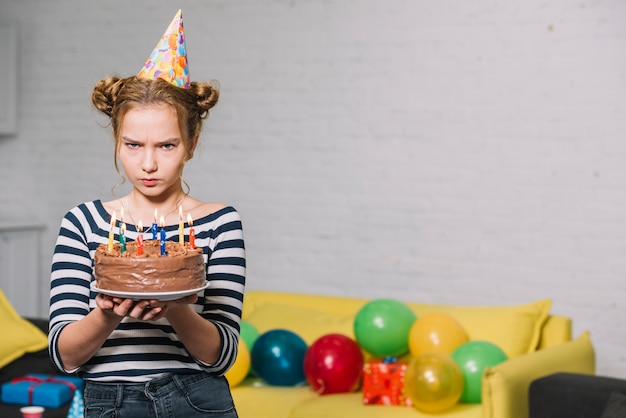 An angry teenage girl wearing party hat holding delicious birthday cake