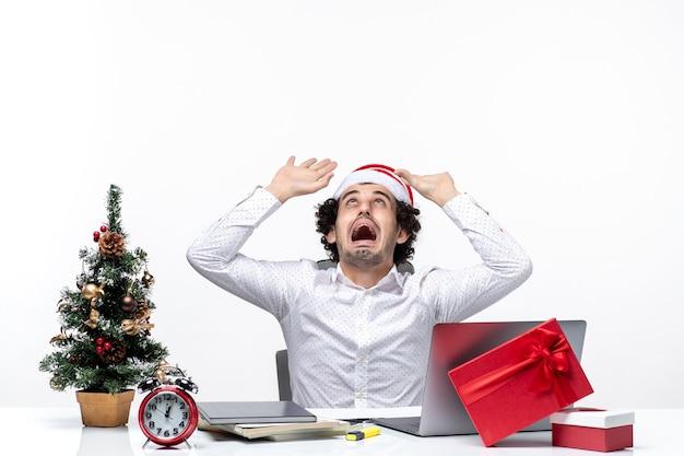 흰색 바탕에 사무실에서 위에 가리키는 재미있는 산타 클로스 모자와 화가 긴장 젊은 사업가