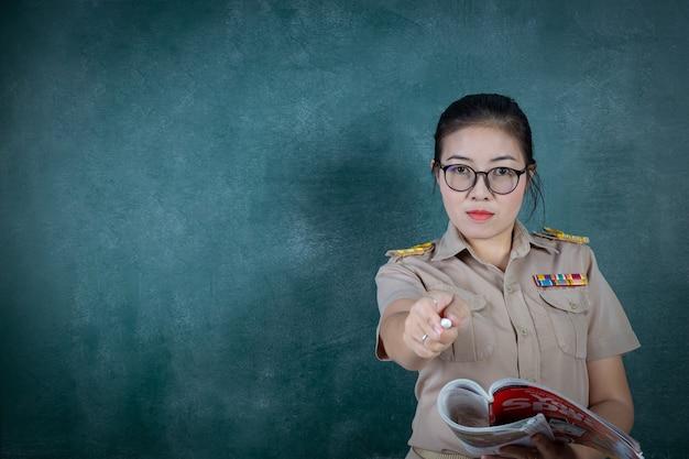 Insegnante tailandese arrabbiato in attrezzatura ufficiale che sta davanti al tabellone che indica dito la macchina fotografica