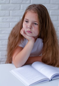 An angry and tired schoolgirl studies with a book on her desk.