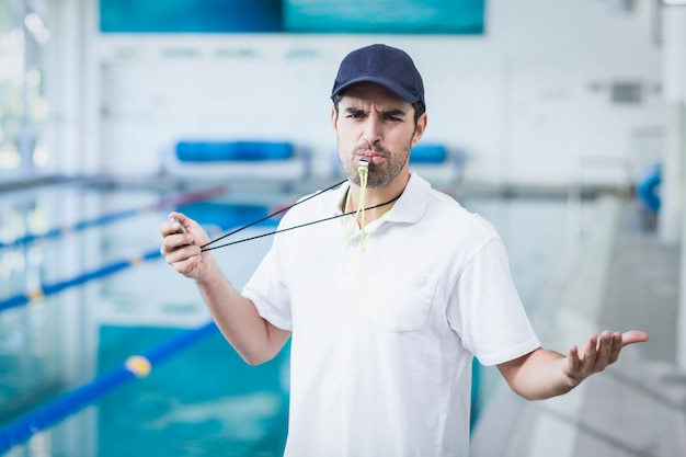 Angry trainer blowing whistle and holding stopwatch at the pool
