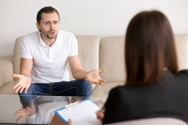 Angry troubled man complaining to female psychotherapist, talking about problems