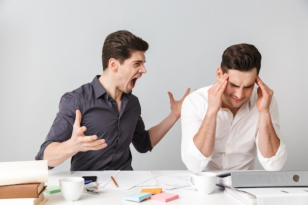 Angry two young business men talking with each other swear.