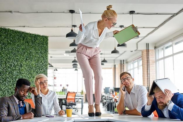 Злая неуравновешенная начальница кричит, ругает сотрудников за невыполнение плана на работе.