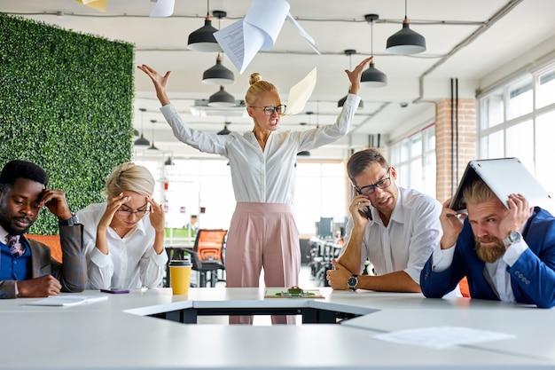 Сердитая неуравновешенная женщина-босс кричит, ругает сотрудников за невыполнение плана на работе