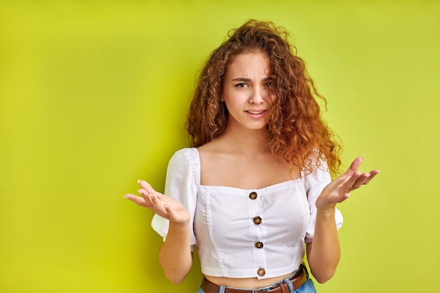 Angry unhappy young woman with arms out asking what is problem on green