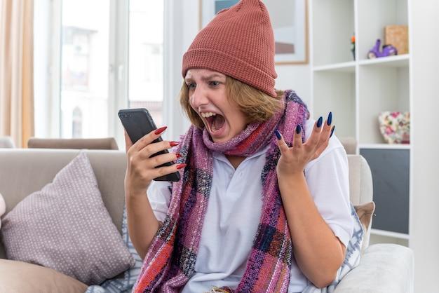 밝은 거실에서 소파에 앉아 휴대 전화로 이야기하는 동안 감기와 독감 소리로 고통 받고 아픈 목 주위에 따뜻한 스카프로 모자에 화난 건강에 해로운 젊은 여성