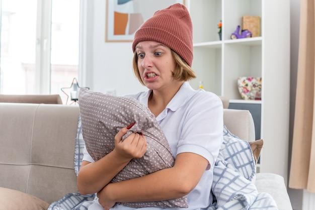 暖かい帽子をかぶった暖かい帽子をかぶった怒っている不健康な若い女性が、毛布が具合が悪く、風邪やインフルエンザに苦しんでいる病気に見え、明るいリビングルームのソファに積極的な表情で座っている