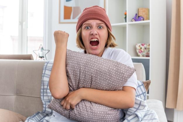 毛布を着た暖かい帽子をかぶった怒った不健康な若い女性が、風邪やインフルエンザに苦しみ、枕を持ち、明るいリビングルームのソファに座って攻撃的な表情で拳を握りしめている