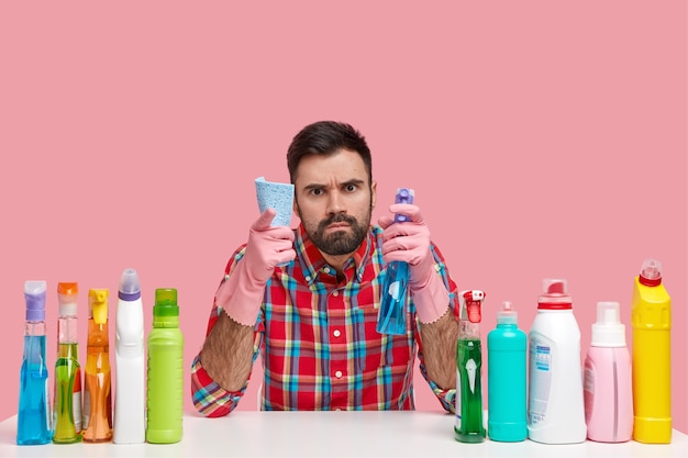 Angry unshaven busy man looks with gloomy expression, points with index finger , holds mop, spray, dressed in checkered shirt