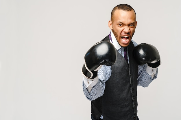 Angry upset young man office worker, business employee, fists in air with boxing gloves, open mouth yelling and shouting, negative emotion facial expression feeling.