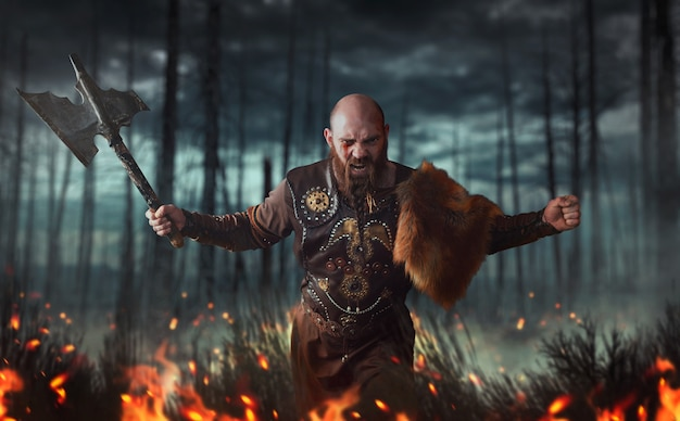 Злой викинг с топором, одетый в традиционную скандинавскую одежду, сражается в огне