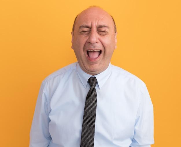 Сердитый мужчина средних лет с закрытыми глазами в белой футболке с галстуком изолирован на оранжевой стене