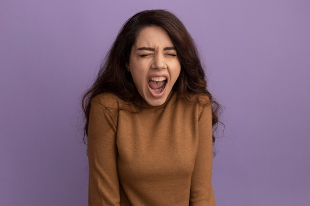 紫の壁に隔離された茶色のタートルネックのセーターを着た美しい少女を目を閉じて怒っている