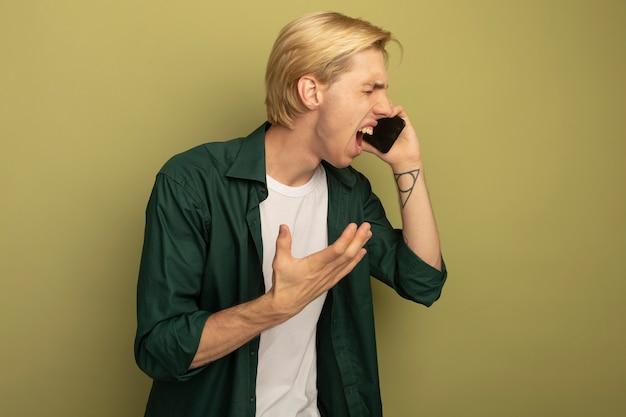 닫힌 된 눈으로 화가 녹색 티셔츠를 입고 젊은 금발의 남자가 전화로 말한다