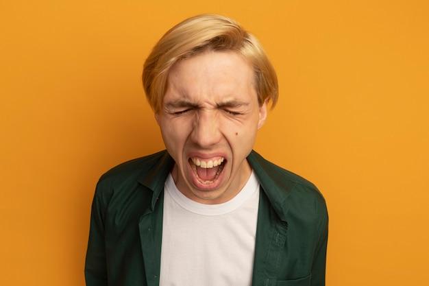 Arrabbiato con gli occhi chiusi giovane ragazzo biondo che indossa la maglietta verde