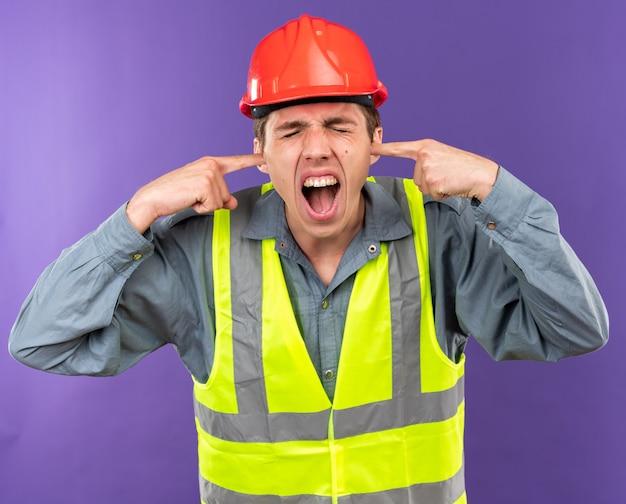닫힌된 눈으로 화난 제복을 입은 젊은 건축업자 남자 닫힌 귀