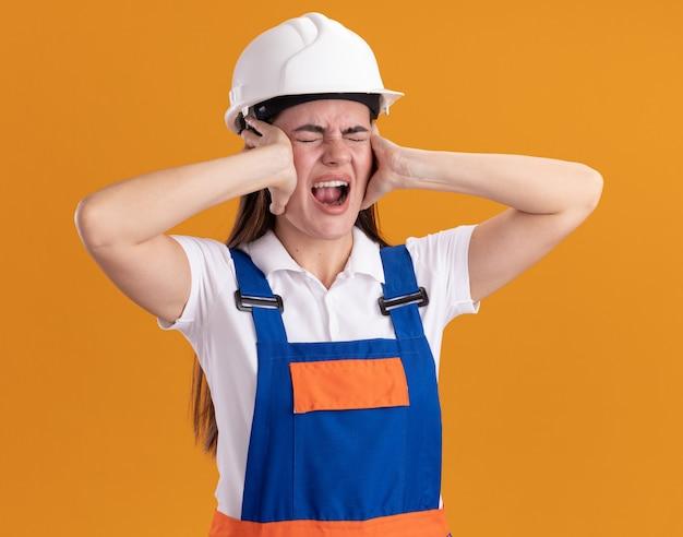 Arrabbiato con gli occhi chiusi giovane donna costruttore in uniforme che mette le mani sulle orecchie isolate sul muro arancione