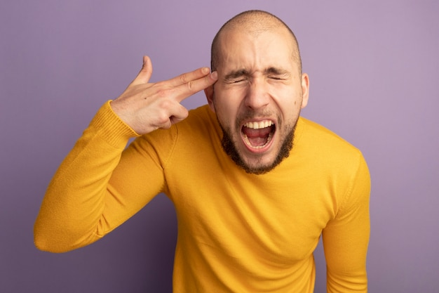 目を閉じて怒っている若いハンサムな男は紫色の壁に分離されたピストルジェスチャーで自殺を示しています