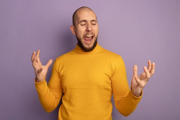 目を閉じて怒っている若いハンサムな男が紫色の壁に孤立した手を広げ