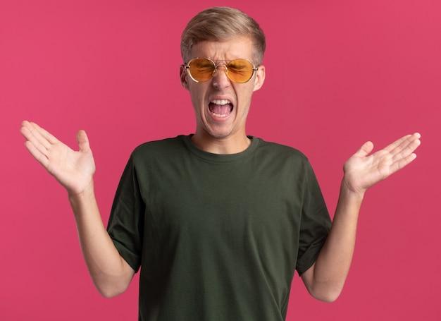 Arrabbiato con gli occhi chiusi giovane bel ragazzo che indossa la camicia verde e occhiali diffondendo le mani isolate sul muro rosa