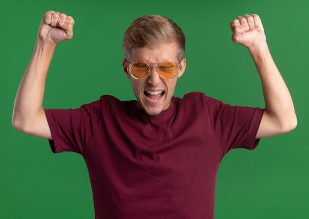 Сердитый с закрытыми глазами молодой красивый парень в красной рубашке и очках, поднимающий кулаки, изолирован на зеленой стене