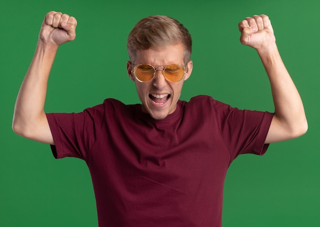 Angry with closed eyes young handsome guy wearing red shirt and glasses raising fists isolated on green wall