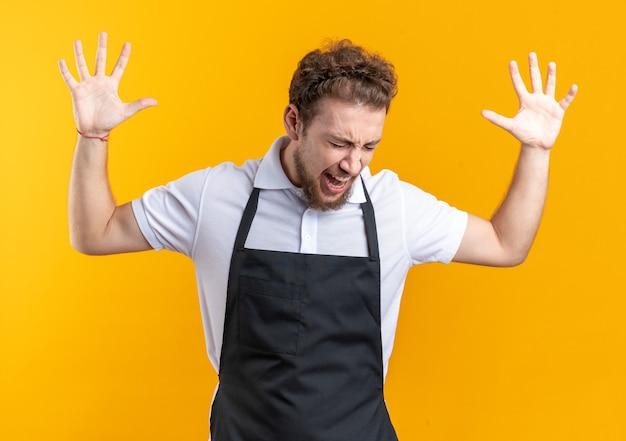 目を閉じて怒っている黄色の壁に隔離された制服を上げる手を身に着けている若い男性理髪師