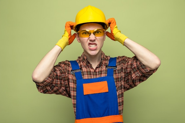 Angry with hands around head young male builder wearing uniform and gloves with glasses
