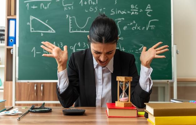 Arrabbiato con la testa abbassata, giovane insegnante femminile si siede a tavola con materiale scolastico allargando le mani in classe