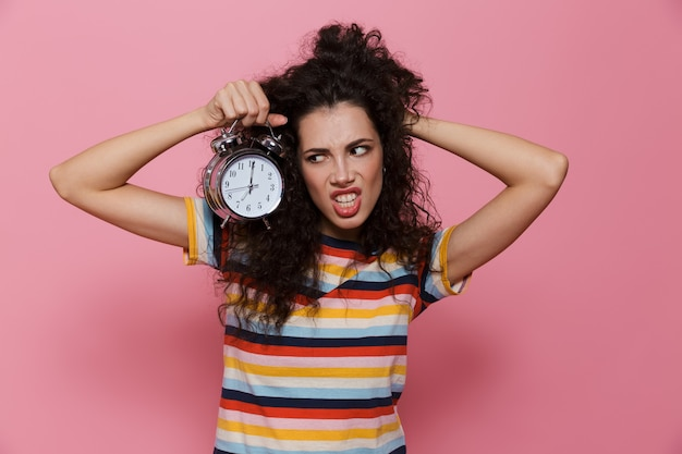 Angry woman 20s with curly hair holding alarm clock isolated on pink