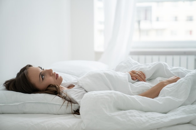 Angry woman annoyed by loud neighbors, looking up suffering from insomnia or stress, lying in bed.