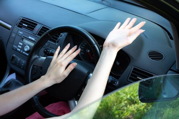 ハンドルの後ろの怒っている女性。運転中の不明な状況。