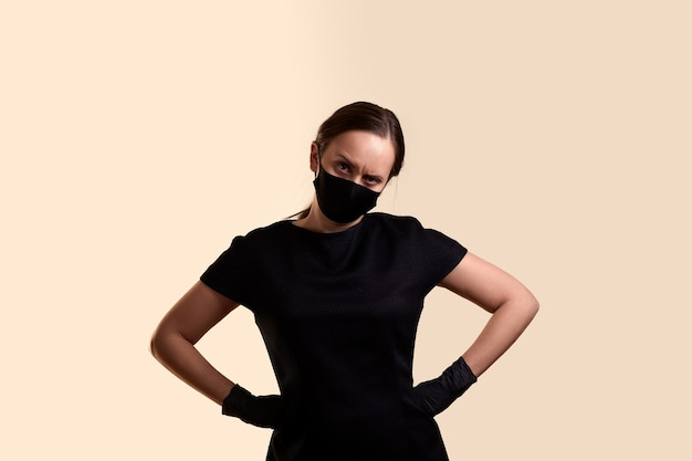 Angry woman in black dress face mask and latex gloves standing with arms akimbo bowing her head and  over beige wall