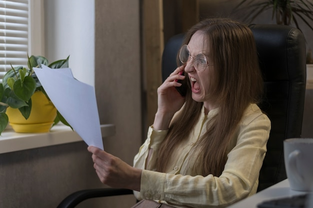 Angry woman boss talking on  phone and shouting, holding documents. director scolds subordinates on smartphone.