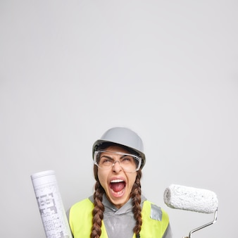 Angry woman builder works on renovation and apartment interior holds roller for painting walls rolled blueprints focused above exclaims loudly isolated over white background. redecoration repair