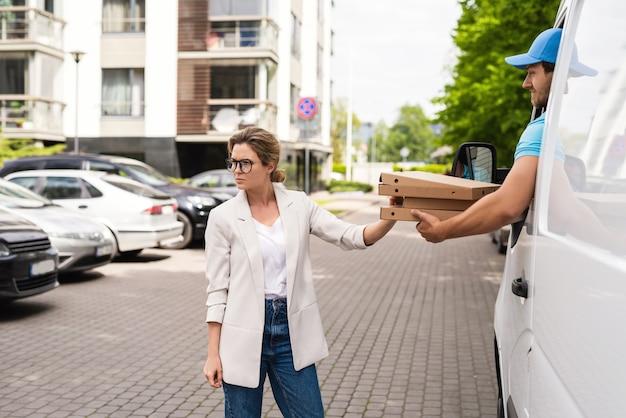 宅配便が間違ったピザを持ってくるか、彼がするので怒っている女性のクライアント