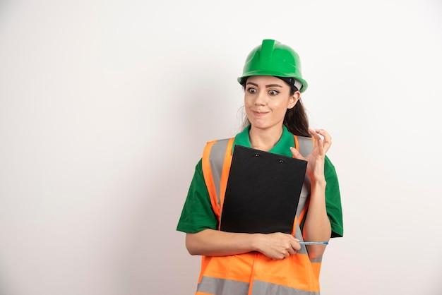 白い背景にクリップボードで怒っている女性エンジニア。高品質の写真