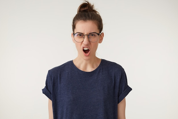Angry woman in glasses with grumpy grimace on her face,with mouth opened