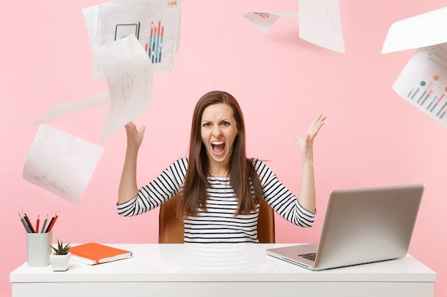 Angry woman having problems screaming throwing up paper documents while working on project, sitting at office with laptop isolated on pink background. achievement business career concept. copy space.