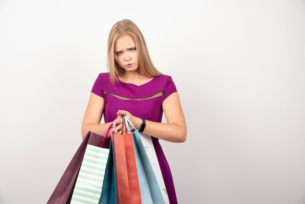 Сердитая женщина, держащая кучу хозяйственных сумок. фото высокого качества