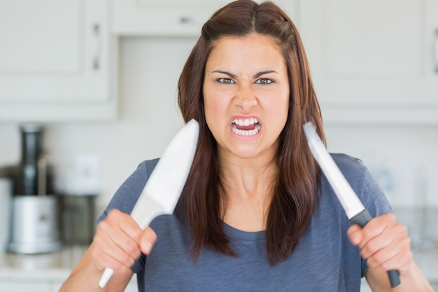 Angry woman holding up knives