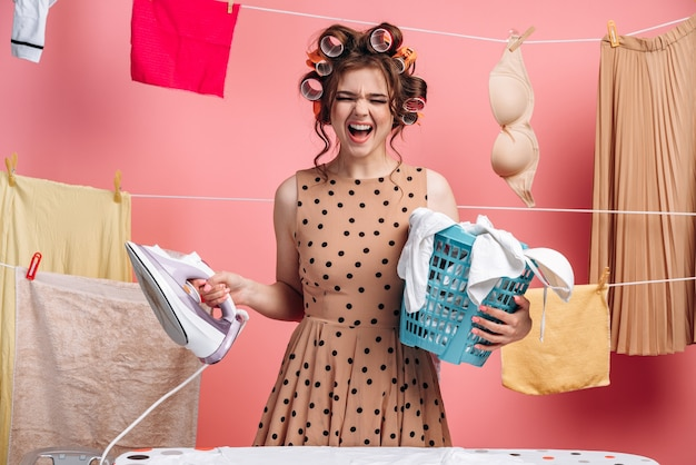 Angry woman housewife in polka dot dress with baskets and iron in hands on a background of ropes with clothes on a pink background. cleaning concept.